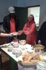 Eine junge Afrikanerin teilt die selbst gekochte Suppe aus