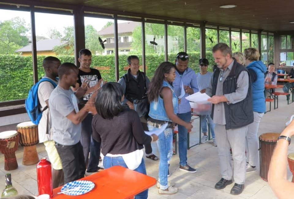 Der Veranstalter des Sprachkurses überreicht den Teilnehmern ihr Zertifikat.